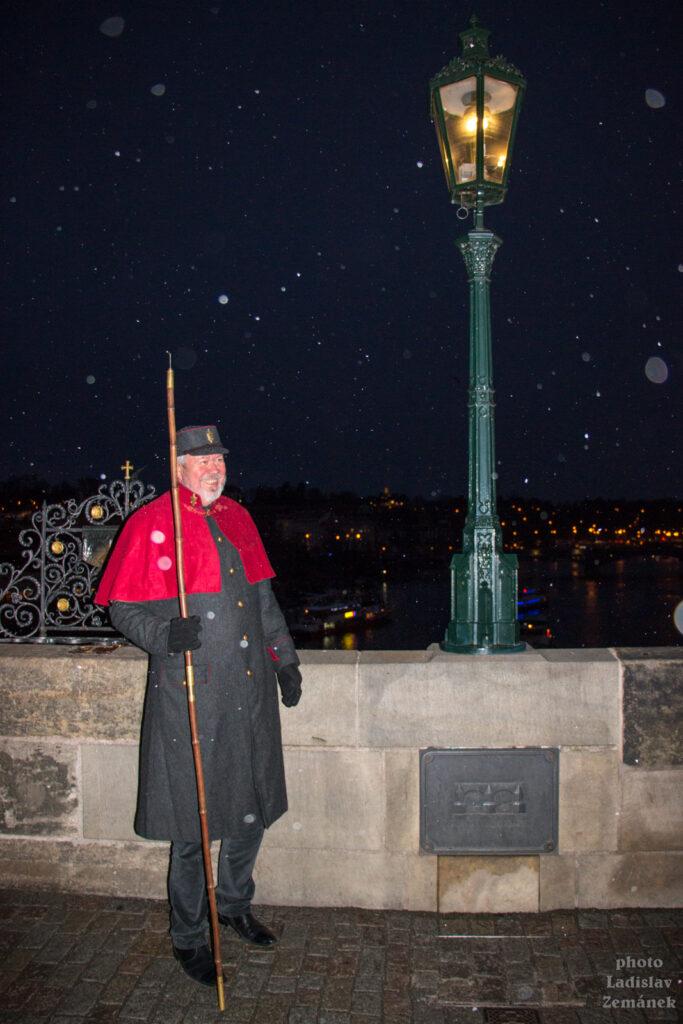 Advent v Praze - Lampář rozsvěcí plynové lampy na Karlově mostě