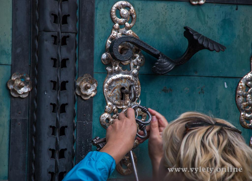 Průvodkyně odemyká vysoké dveře